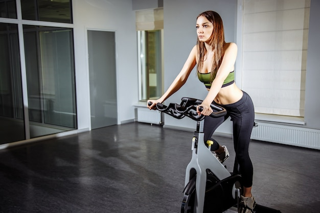 Young woman working out on the exercise bike at the gym
