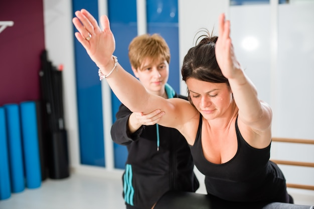 Young woman working out hard on pilates chair with instructor at gym