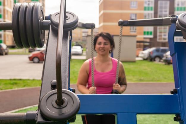 屋外のストリートウェイトマシンで運動している若い女性、運動器具に焦点を当てる