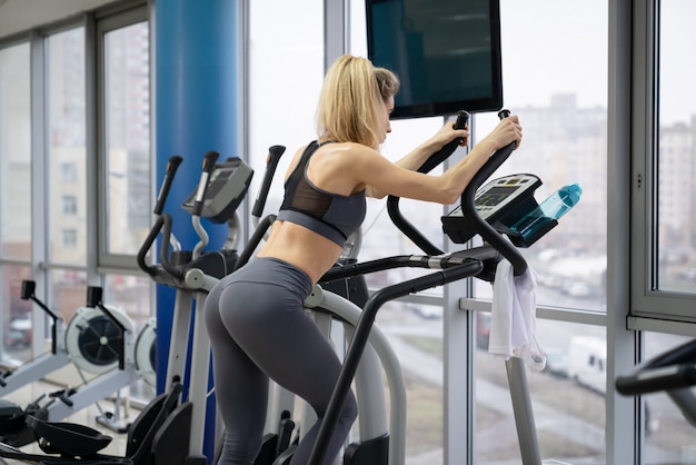 Young woman working out on stepper at gym