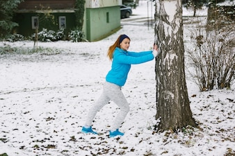 Young woman working out under the tree on snowy landscape