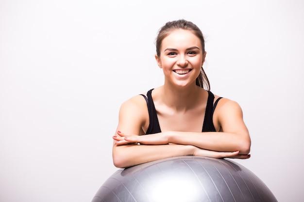 Giovane donna che lavora con una palla isolata su un muro bianco