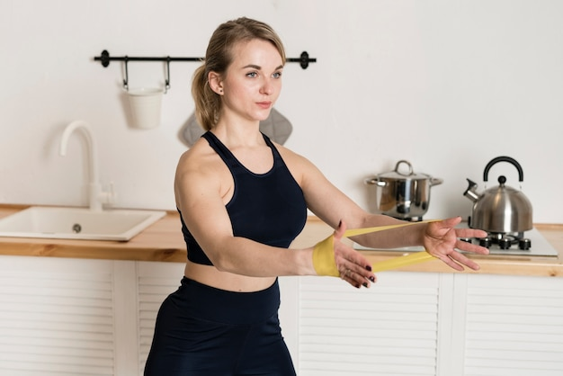 Young woman working out with elastic bands