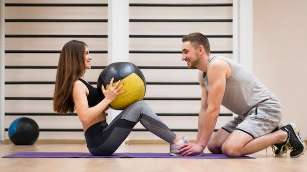 그녀의 트레이너와 함께 운동하는 젊은 여자