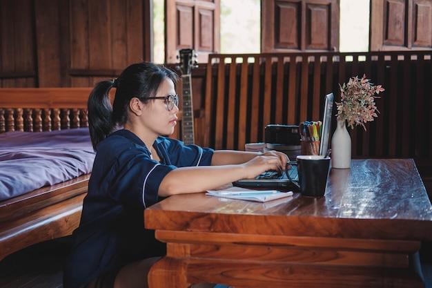 Молодая женщина работает сидя на диване с ноутбуком у себя дома