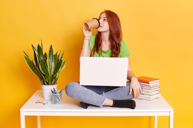 Young woman working or studying against yellow wall, drinking coffee or tea, ginger girl has break, looking away, sitting on table near flower pot, stack of books, pens.