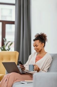 Молодая женщина работает, сидя на диване