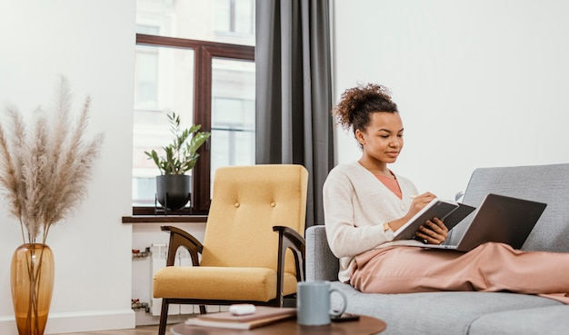 Young woman working while sitting on the sofa