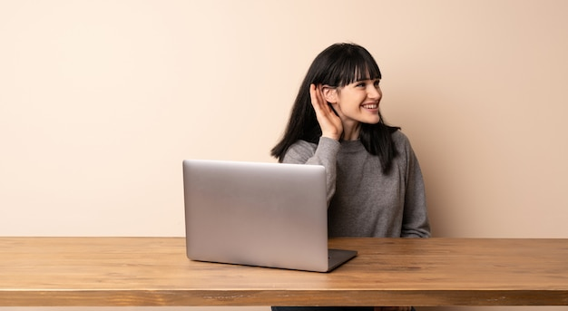 Young woman working with her laptop listening to something by putting hand on the ear
