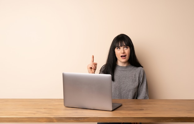 Young woman working with her laptop pointing up and surprised