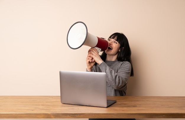 Young woman working with her laptop shouting through a megaphone