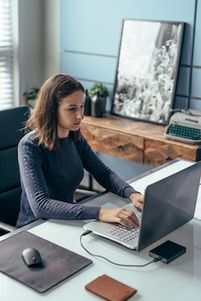 Young woman working with laptop at desk.