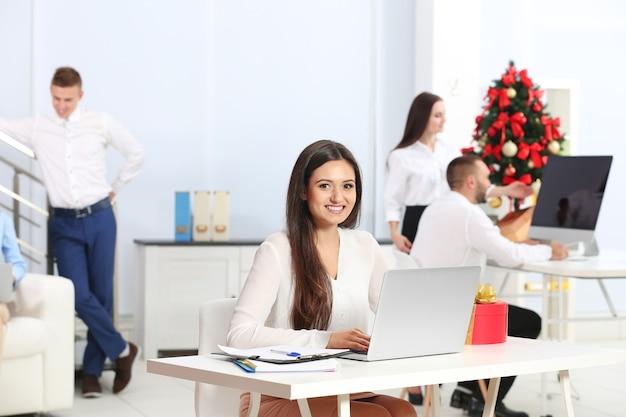 Молодая женщина, работающая с ноутбуком в офисе, украшенном на рождество