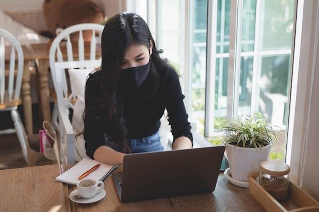 自宅の木製テーブルでノートパソコンで作業している若い女性