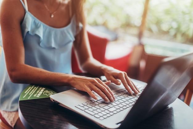 カフェに座ってラップトップで働く若い女性。
