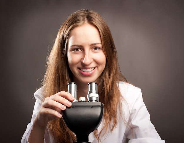 Young woman working with a microscope