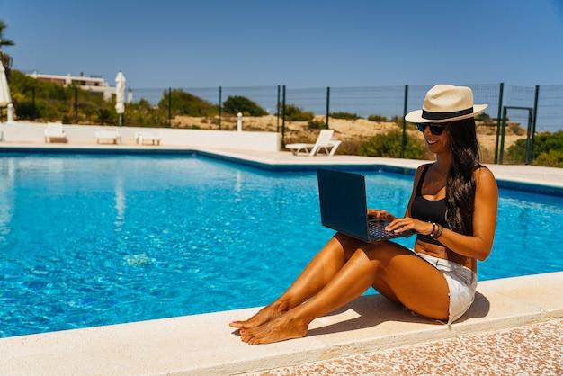 スイミングプールの近くのラップトップで働く若い女性