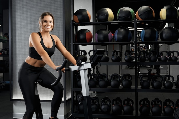 Young woman workout on exercise bike