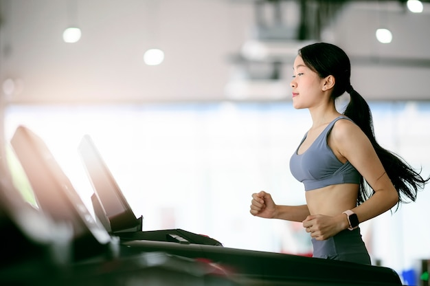 Young woman workout in gym healthy lifestyle, using running machine