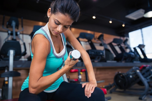 Young woman workout with dumbbell on the bench in gym