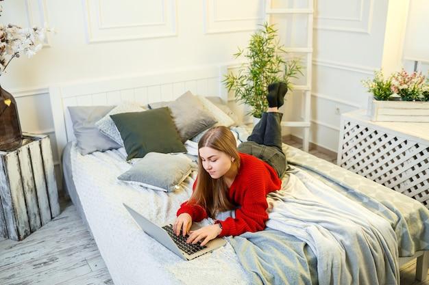 젊은 여성은 컴퓨터에서 일하고, 침대에 앉아 멀리서 일합니다. 긴 머리에 빨간 스웨터와 청바지를 입은 소녀가 집에서 일합니다.
