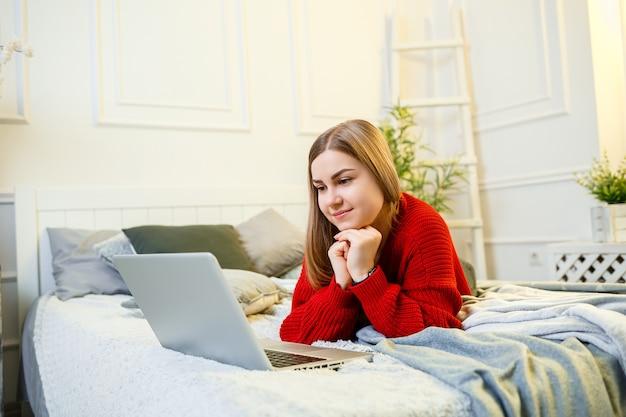 若い女性は、コンピューターで働き、ベッドに座って、遠くから働いています。赤いセーターとジーンズを着た長い髪の少女が家で働いています。