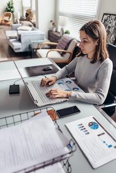 Молодая женщина работает за столом в своем домашнем офисе