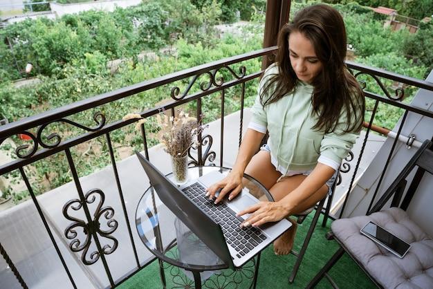 젊은 여자는 테라스 원격 작업 개념에 노트북에서 작동