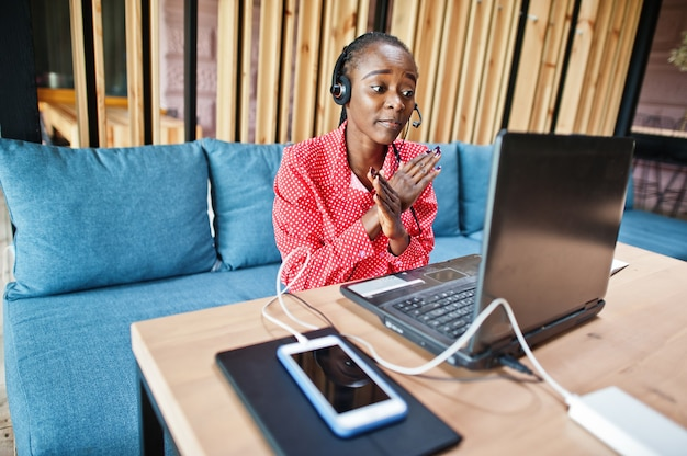 Young woman works in a call center operator and customer service agent wearing microphone headsets working on laptop