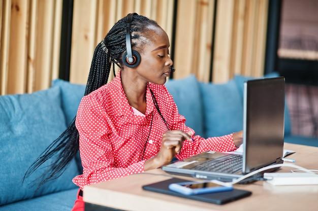 若い女性は、ラップトップで動作するマイクヘッドセットを身に着けているコールセンターのオペレーターとカスタマーサービスエージェントで働いています