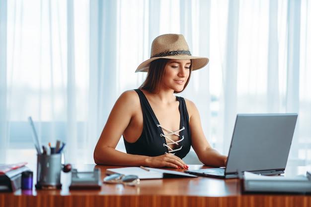 Молодая женщина работает на ноутбуке за столом в офисе и мечтает об отпуске