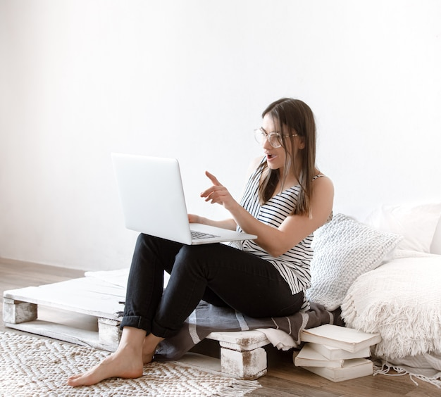 Молодая женщина работает удаленно на компьютере дома.