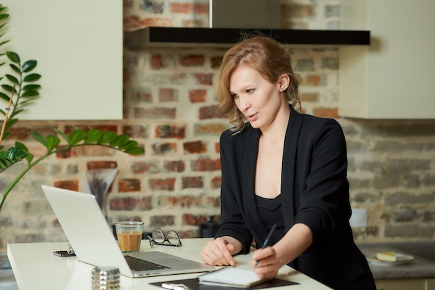 A young woman works remotely in her kitchen. a charming girl doing notes in a notebook and talking to colleagues during a video conference at home.