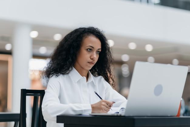 Молодая женщина работает, сидя за столом в фуд-корте