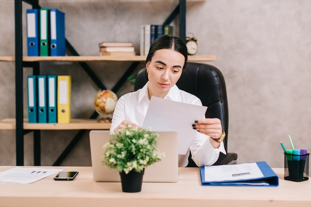若い女性はオフィスでドキュメントを操作します