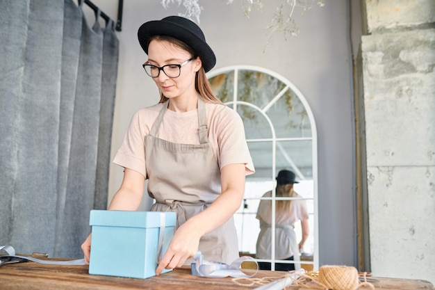 Young woman in workwear and hat standing by wooden table and tying blue giftbox with silk ribbon