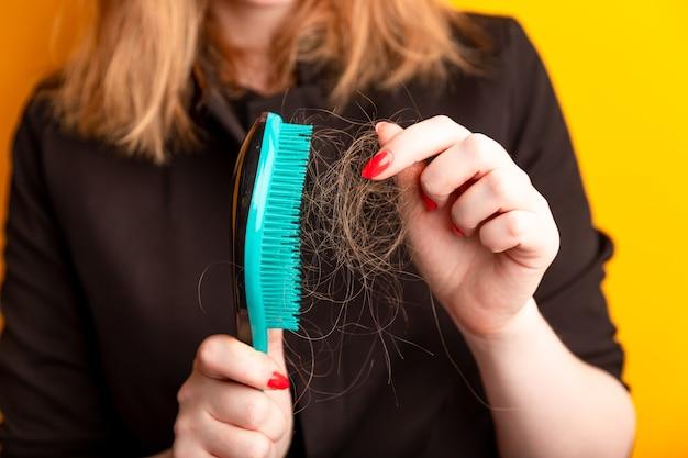 Молодая женщина беспокоится о выпадении волос на желтой стене.