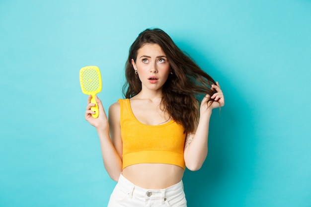 Young woman worried about her hair condition, showing brush and looking at upper left corner with concerned face, standing over blue background.