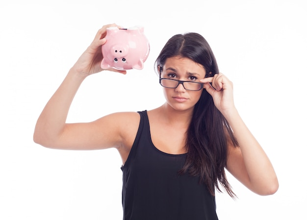 Young woman worried with a piggy bank