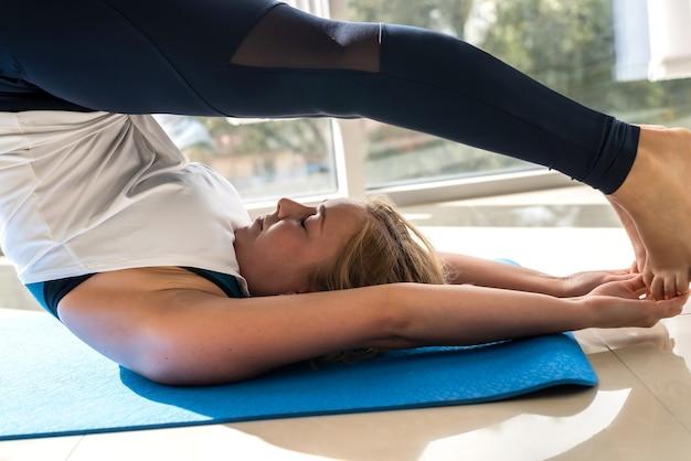 Молодая женщина беспокоится о своем здоровье, делая упражнения медитации и йоги для здоровой спины