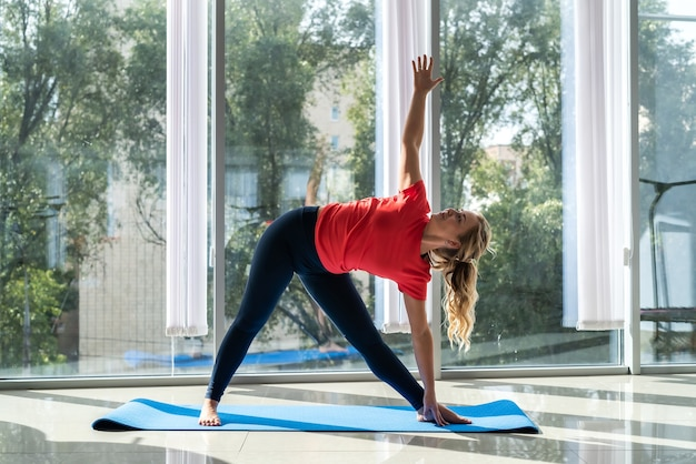 Молодая женщина, беспокоясь о своем здоровье, занимается медитацией и упражнениями йоги для здоровой спины
