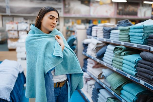 Молодая женщина завернулась в полотенце, магазин постельного белья. женщина покупает товары для дома на рынке, дама в магазине постельных принадлежностей
