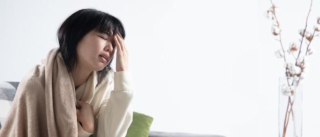 격자 무늬에 싸인 젊은 여성은 집에서 집에 있는 소파에 앉아 아프고, 아프고, 재채기하고, 기침하는 것처럼 보입니다. 건강 관리 및 의학, 질병 예방, 계절 질병 증상 및 자기 보호. 전단