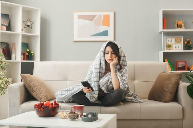 격자 무늬에 싸인 젊은 여성이 거실에 있는 커피 테이블 뒤에 소파에 앉아 전화기를 들고 보고 있습니다.