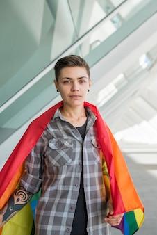 Молодая женщина, завернутая в радужный флаг