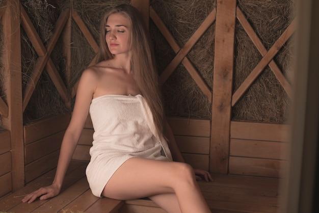 사우나 휴식 수건에 싸여 젊은 여자