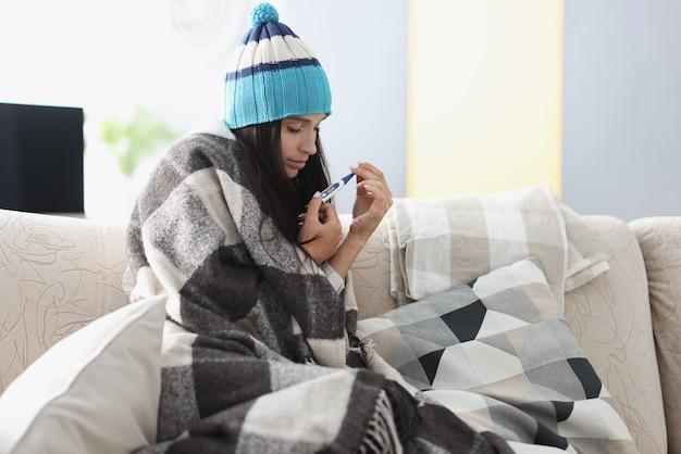 따뜻한 담요에 싸여 젊은 여자는 온도계와 소파에 앉아