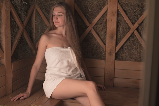 Young woman wrapped in towel relaxing sauna