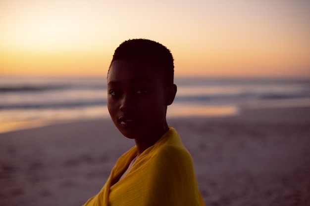 Young woman wrapped in yellow scarf on the beach