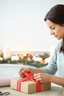 クリスマスプレゼントを包む若い女性